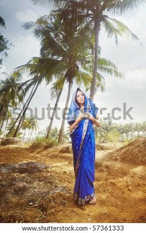 Beautiful lady outdoors in elegant sari walking in the wild jungle - stock photo