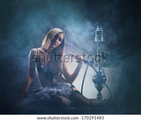 Beautiful lady smoking the hookah over the smoky background   - stock photo