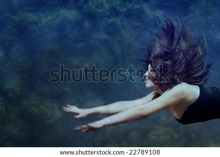Beautiful lady swimming and diving underwater - stock photo