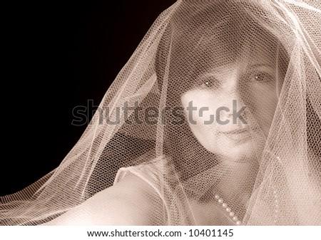 Beautiful lady under a gauzy veil, sepia toned - stock photo