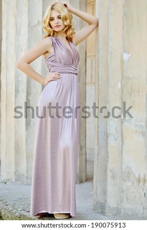 beautiful lady wearing long dress near the columns - stock photo