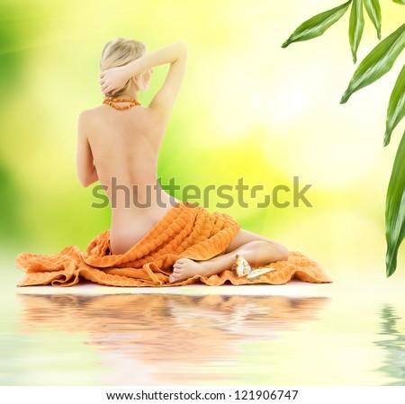 beautiful lady with orange towels on sand - stock photo