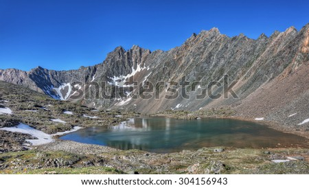 Beautiful lake at the foot of the mountain range. Summer morning in the mountains of Eastern Siberia - stock photo