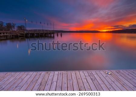 Beautiful lake landscape with vibrant sunset. Long exposure landscape. - stock photo
