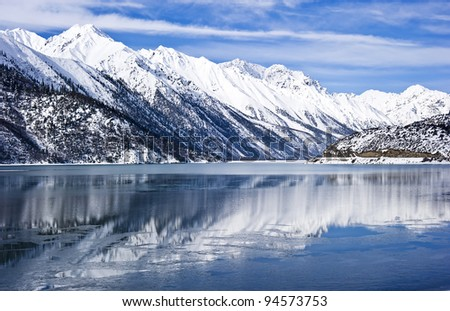 beautiful lake shadow landscape in tibet with blue sky and wonderful cloud - stock photo