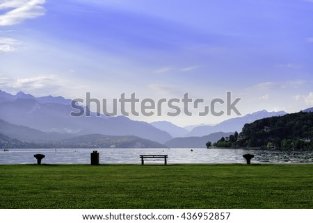 Beautiful lake surrounded by Alps mountains and bench on the grass - stock photo