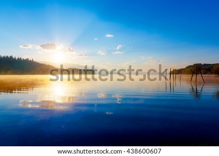 beautiful lake view in morning fog with mystic mountains and trees as leftovers of a mole in gold, purple - blue tones - stock photo
