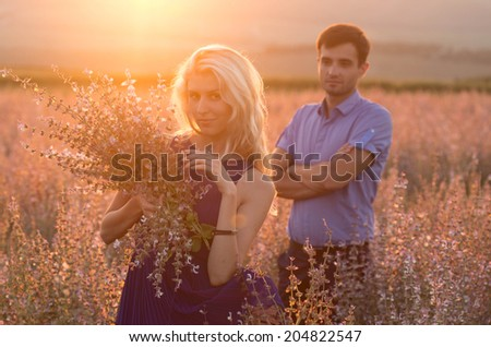 beautiful landscape and couple in love with flowers on sunset - stock photo