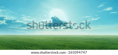 Beautiful landscape. Cloud with sun on blue sky at summer day over the green meadow - stock photo