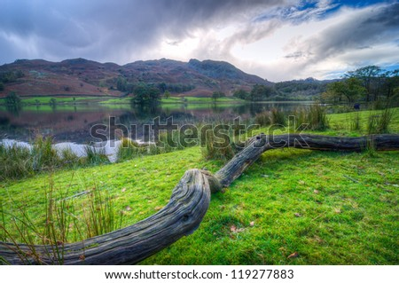 Beautiful Landscape image of Rydal Water in Lake District, a National Park in England, during Autumn with blue/grey sky and view of the distant hills - stock photo