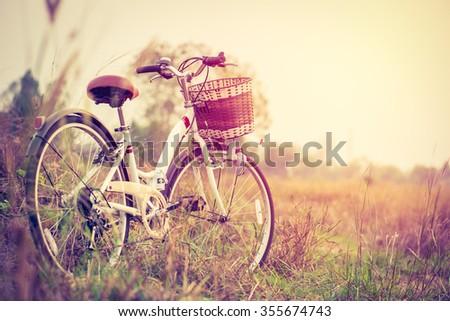 beautiful landscape image with vintage Bicycle at sunset ; vintage tone style - stock photo