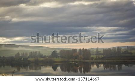 Beautiful landscape in Tasmania, Australia. With a calm lake and the orange sun rising on the background. - stock photo