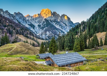 Beautiful landscape in the Alps with traditional mountain chalets and golden glowing summits in beautiful evening light at sunset - stock photo