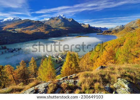 Beautiful landscape in the Swiss Alps on a day in autumn. Misty Sils-Baselgia at lake Sils surrounded by fall colored larches in the upper Engadin. - stock photo
