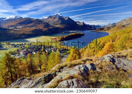 Beautiful landscape in the Swiss Alps on a day in autumn. Sils-Baselgia at lake Sils surrounded by fall colored larches in the upper Engadin. - stock photo