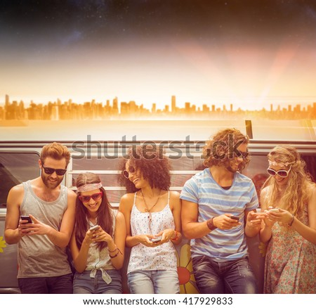 Beautiful landscape of an urban city against hipster friends using their phones - stock photo