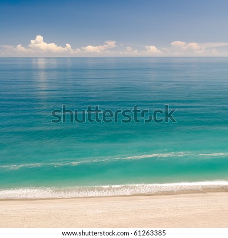 Beautiful landscape of beach with green water and blue sky. - stock photo