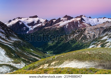 Beautiful landscape of the valley and snowy peak in the distance - stock photo