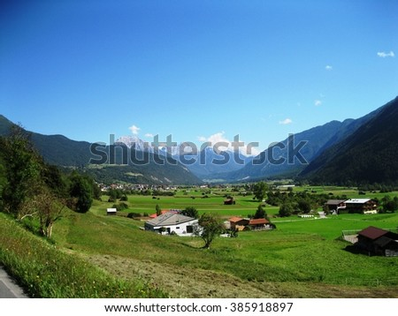 Beautiful landscape of valley in Alpine mountains, small houses in Tirol, rural scene, majestic picturesque view in sunny day  - stock photo