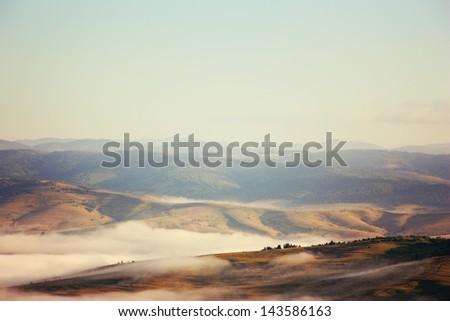 Beautiful landscape panorama with fog - stock photo
