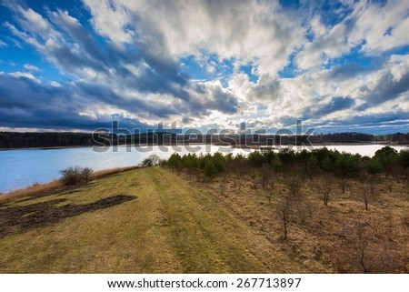 Beautiful landscape photographed from above (from tall observation tower). Early spring meadow on lake shore with forest under blue sky with clouds. Tranquil scene. - stock photo