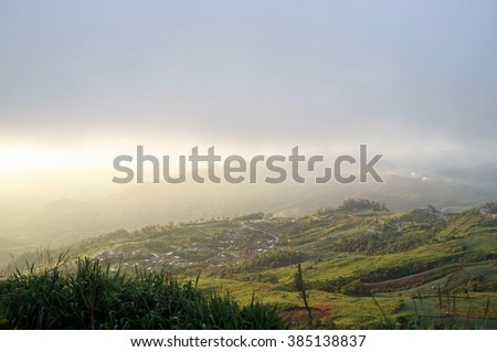 Beautiful Landscape sun rising morning on the mist in the field , take photo on the mountain winter in North Thailand, Phutabberk mountain. - stock photo