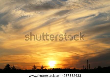 beautiful landscape with a sunset sky over the field - stock photo