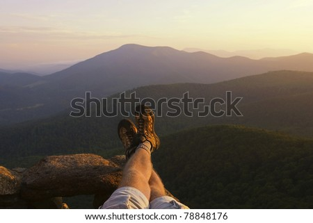 Beautiful landscape with bare legs and boots of hiker in the foreground. - stock photo