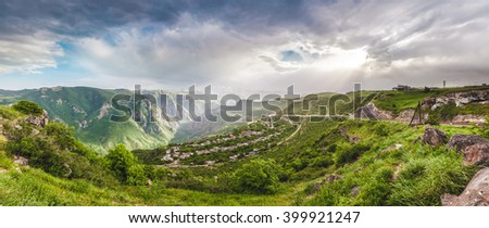 Beautiful landscape with green mountains and magnificent cloudy sky in sunset - stock photo