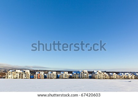 beautiful landscape with housing area in winter and blue sky - stock photo