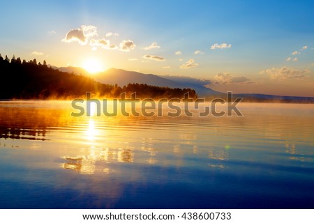 beautiful landscape with mountains and lake at dawn in golden blue and orange tones. Slovakia, Central Europe, region Liptov - stock photo