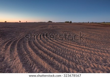 Beautiful landscape with plowed field under sunset or sunrise sky. Agriculture of Poland. - stock photo