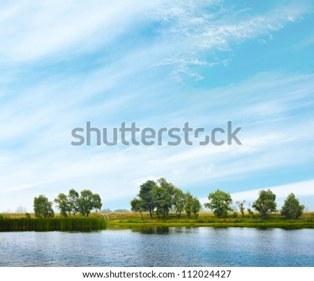 beautiful landscape with trees, sky and water - stock photo