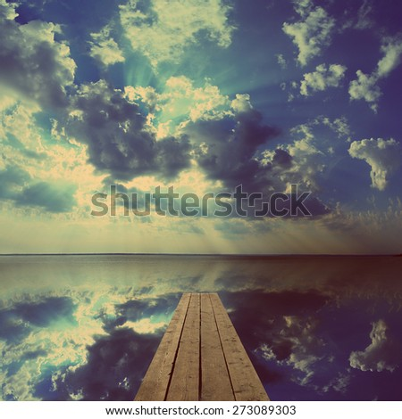 beautiful landscape with wooden pier on big lake and sky reflection - vintage retro style - stock photo