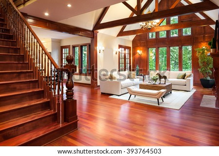 Beautiful large living room interior with hardwood floors and fireplace in new luxury home. Includes vaulted ceilings with trusses and stairway. - stock photo