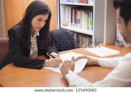 Beautiful latin businesswoman signing a contract - stock photo