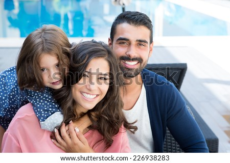 Beautiful latin family relaxing close to the pool - stock photo