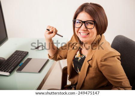 Beautiful Latin retoucher using a pen tablet for work and smiling - stock photo