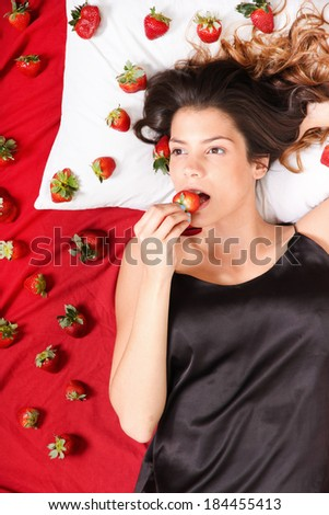 Beautiful, latin Woman eating a Strawberry in bed.  - stock photo