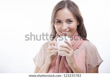 Beautiful latin woman enjoying a hot beverage and smiling - stock photo