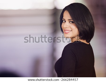 Beautiful latin woman looking back and smiling  - stock photo