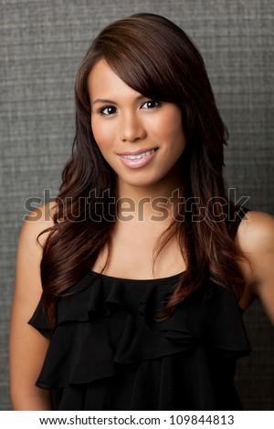 Beautiful Latina woman with long dark hair wearing black shirt and short on textured grey background, shot in studio. - stock photo