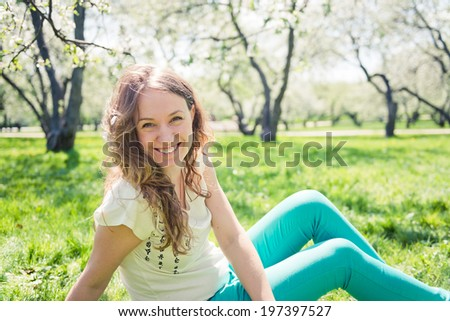 Beautiful laughing girl in green jeans sits on green grass.  - stock photo