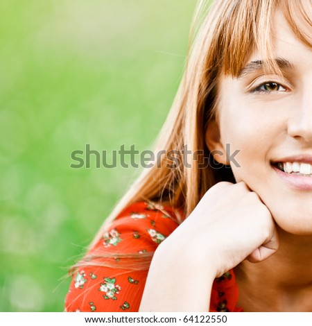 Beautiful laughing girl in red dress sits on green grass. - stock photo
