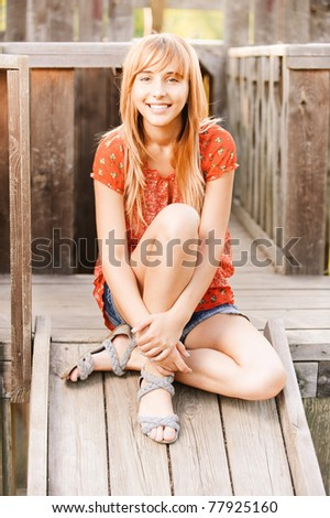 Beautiful laughing girl in red dress sits on wooden ladder. - stock photo