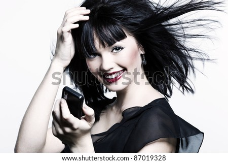 beautiful laughing girl with perfect skin and bright red lipstick, black straight hair in the wind, developing, and with the phone in his hand on a white background - stock photo
