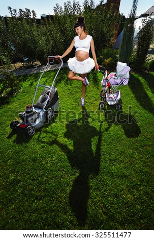 Beautiful laughing pregnant woman  with lawn mower and baby carriage near country house. - stock photo