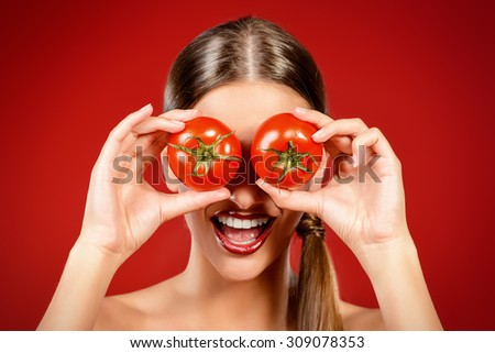 Beautiful laughing woman holding two ripe tomatoes before her eyes. Red background. Healthy eating concept. Diet. - stock photo