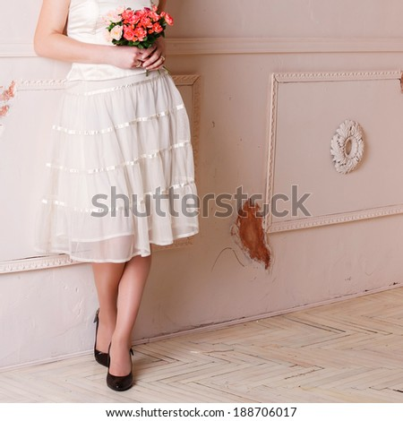 Beautiful leg of the young bride. Women making adjustment to wedding gown in professional fashion designer studio  - stock photo