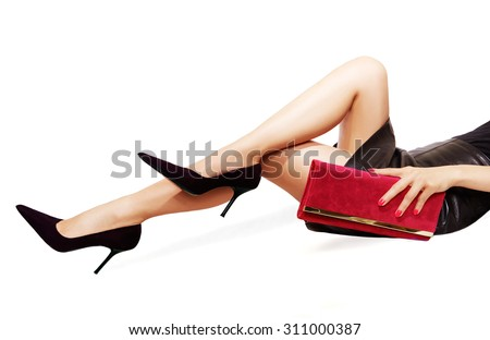 Beautiful legs wearing sexy black high heels. hand holding a red purse. Isolated on white.  - stock photo